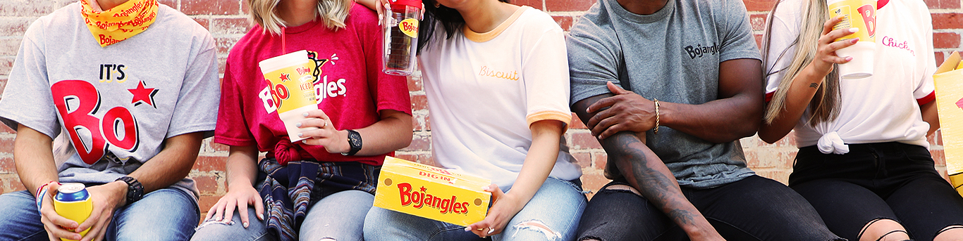 Group of people against a brick backdrop waving Bojangles tees and merchandise