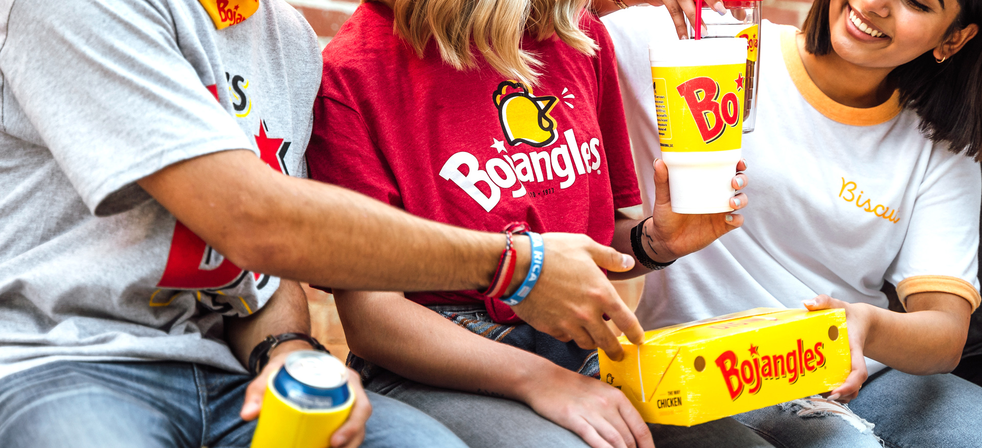 3 friends wearing Bojangles merchandise and sharing food and drinks