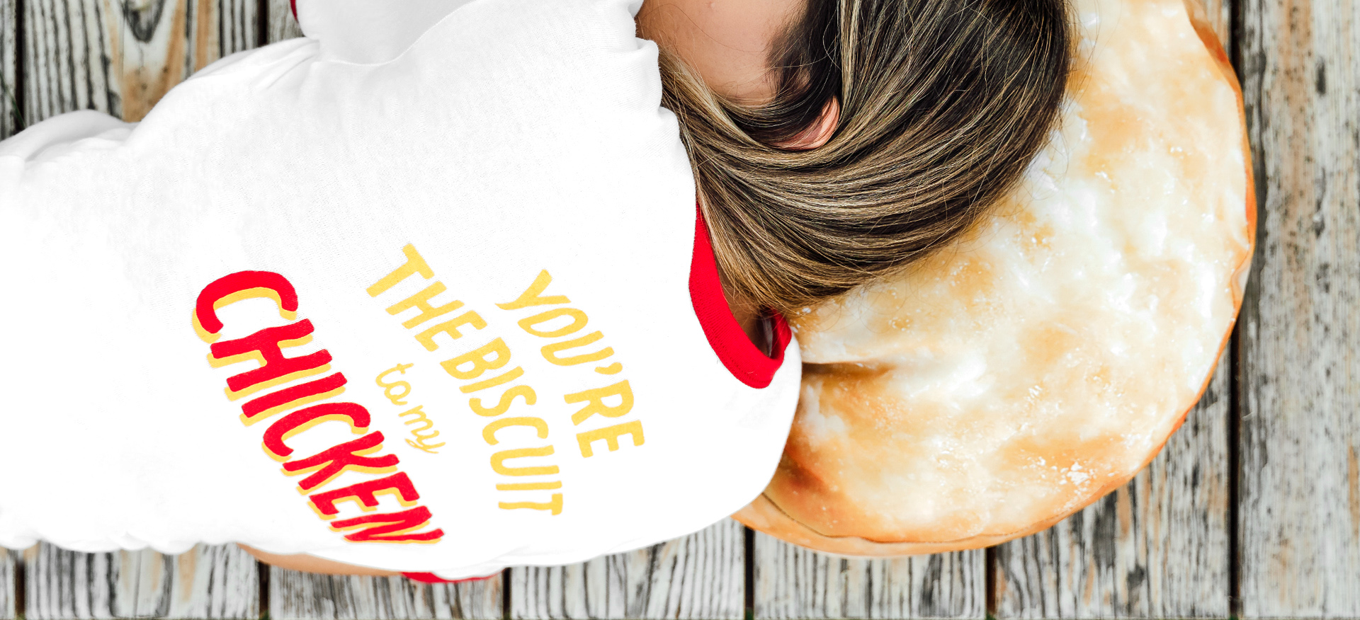 Woman resting on wood bench laying on Bojangles Biscuit Pillow wearing You're the Biscuit to My Chicken Tee