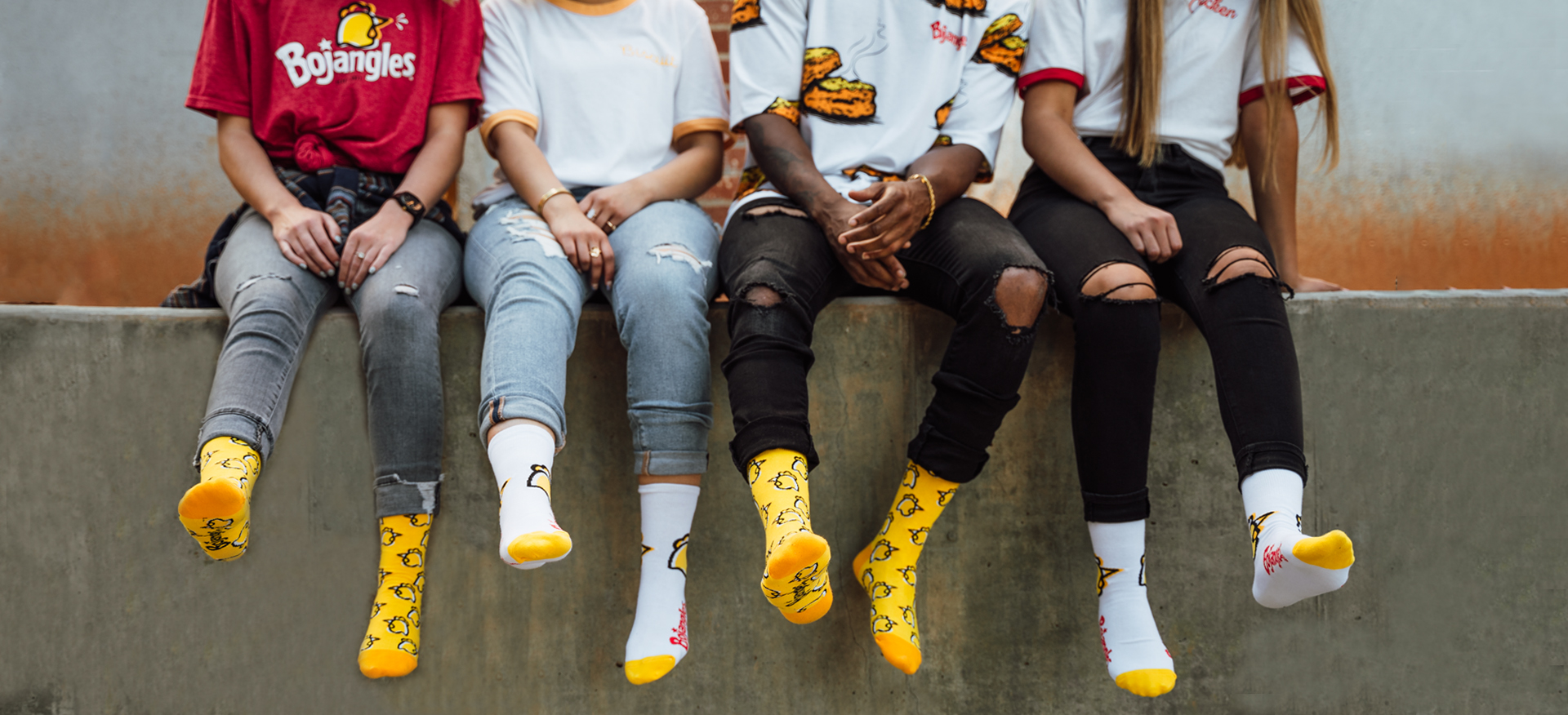 Group of people on a wall wearing variety of Bojangles shirts and each wearing dress or crew socks swinging feet